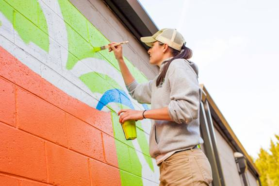 President Lanie Whitaker adds her creative touches to the mural.