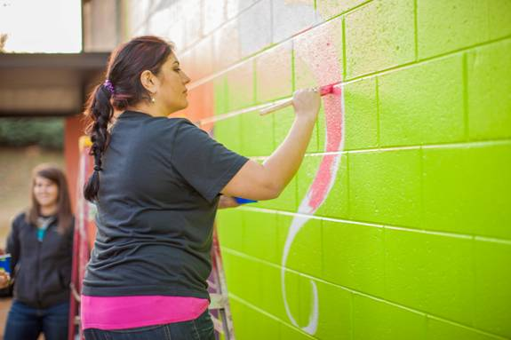 Junior and mural designer Ana Cordoba paints precisely onto her work of art.